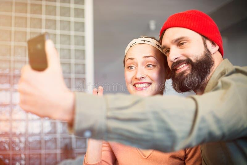 Serrage des moments heureux Beaux jeunes couples affectueux collant entre eux et faisant le selfie tout en se reposant sur le sof photo stock