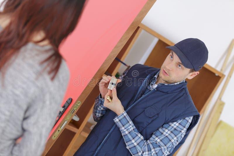 Serralheiro alegre que instala a fechadura da porta perto do cliente fêmea fotos de stock royalty free