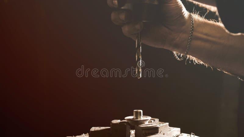 Serralheiro que parafusa uma broca em uma máquina de furo fotografia de stock