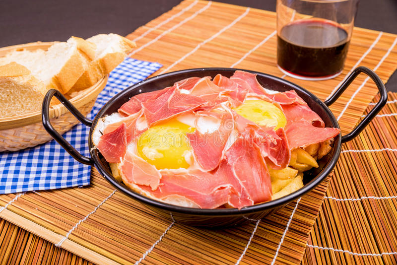 Serrano ham with eggs. Small tapa sized casserole with a serving of serrano ham with eggs stock photography