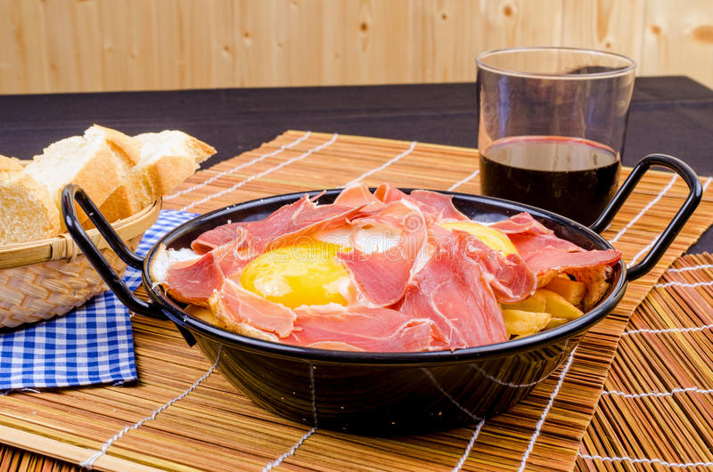 Serrano ham with eggs. Small tapa sized casserole with a serving of serrano ham with eggs royalty free stock image