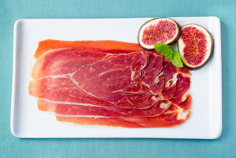 Serrano Ham with Figs. Serrano cured ham with sliced figs and mint leaves royalty free stock image