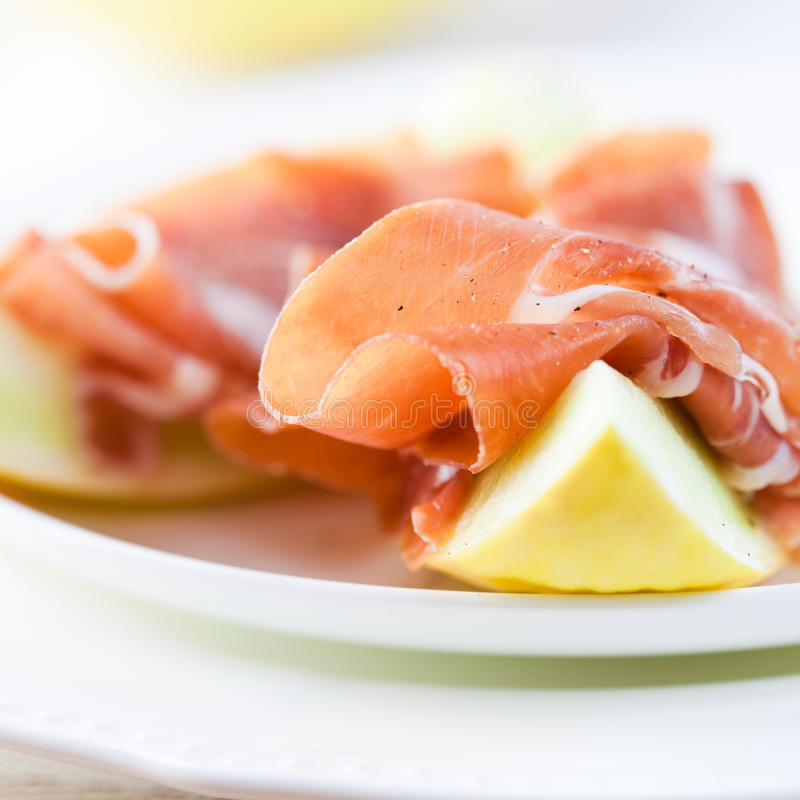 Serrano ham with melon. Close up of spanish serrano ham with melon sprinkled with black pepper royalty free stock image