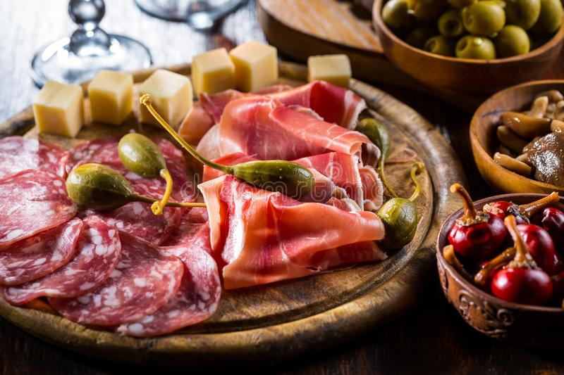 Serrano ham platter with variation of appetizers. On wooden background stock images