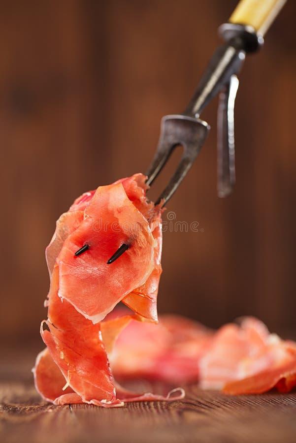 Serrano jamon kurerat kött på stor gaffel royaltyfri fotografi