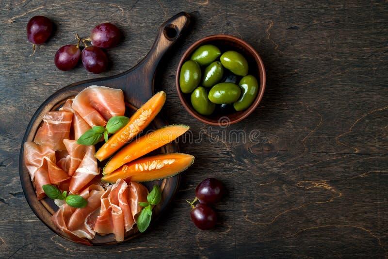 Serrano ou prosciutto de Jamon com melão e azeitonas sobre o fundo de madeira rústico Antipasti italianos ou espanhóis foto de stock