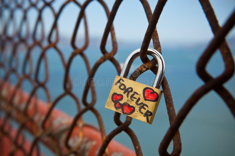 Serratura di amore di forever al ponticello di cancello dorato fotografia stock