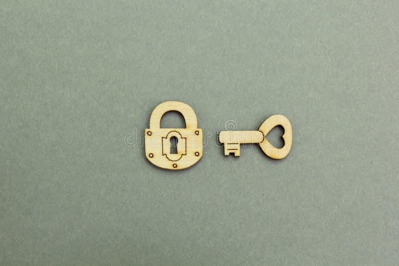 Serratura di legno e chiave su un fondo grigio fotografia stock libera da diritti
