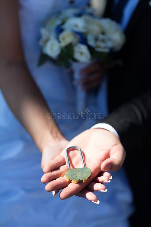 Serratura di nozze nelle mani delle persone appena sposate immagini stock libere da diritti