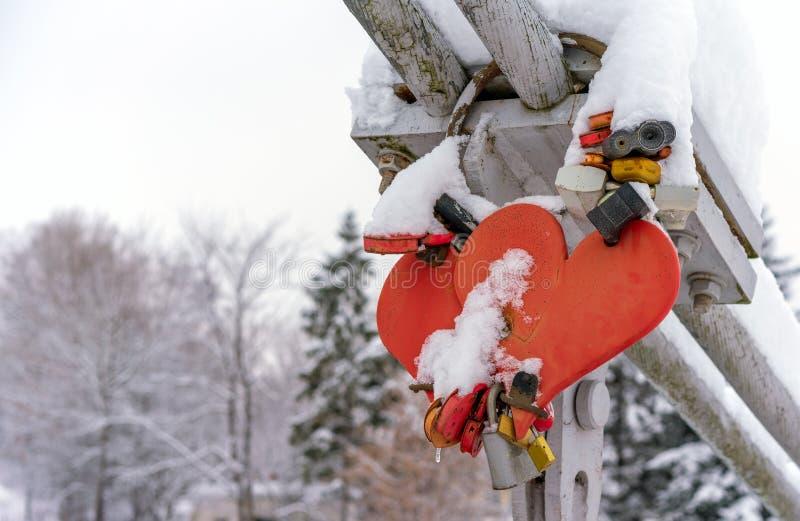 Serrature di nozze e cuori di nozze coperti di neve sul parapetto del ponte sopra il fiume congelato in una piccola città russa d immagini stock libere da diritti