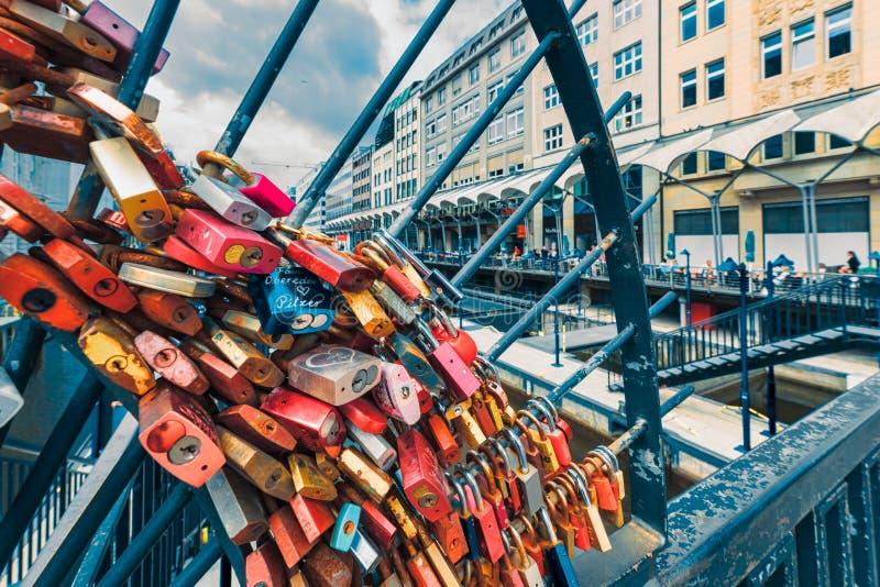 Serrature variopinte di amore ad una griglia del ferro a Jungfernstieg fornire prova delle visite alla città immagini stock