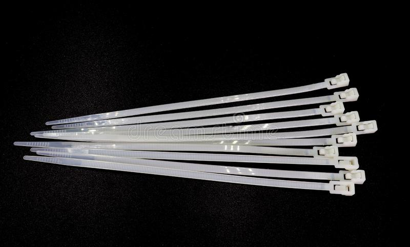 Serre-câble en nylon blanc d'isolement sur un fond noir photos stock