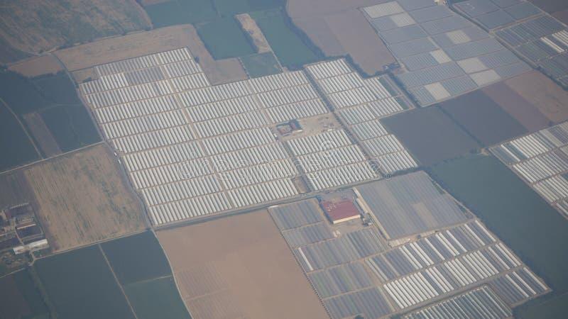 Serres chaudes et champs cultivés des fenêtres d'avion pendant l'heure d'été photo stock