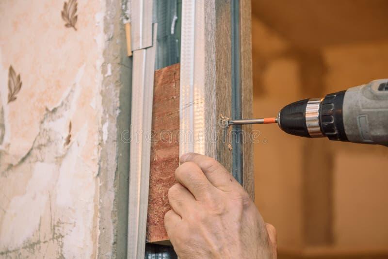 Serrez les vis Vissez les vis avec l'outil Réparation dans l'appartement Installation de porte Travail de serrurier image libre de droits