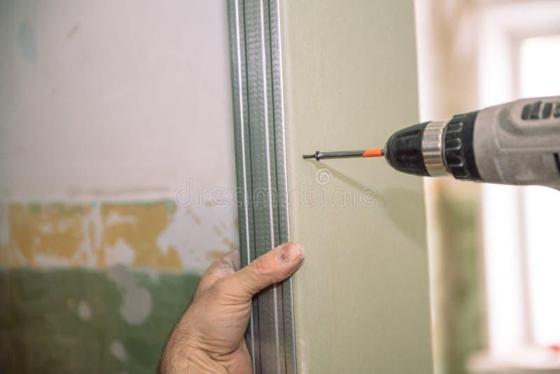 Serrez les vis Vissez les vis avec l'outil Réparation dans l'appartement Installation de porte Travail de serrurier photo stock