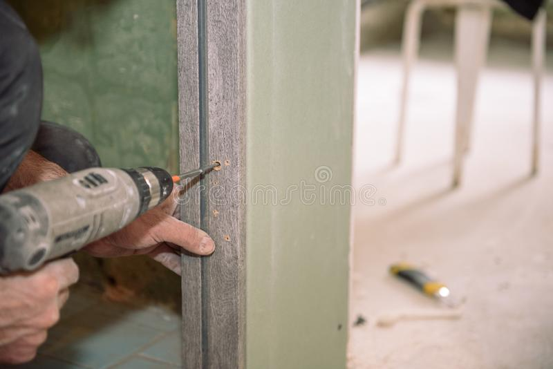 Serrez les vis Vissez les vis avec l'outil Réparation dans l'appartement Installation de porte Travail de serrurier photos libres de droits