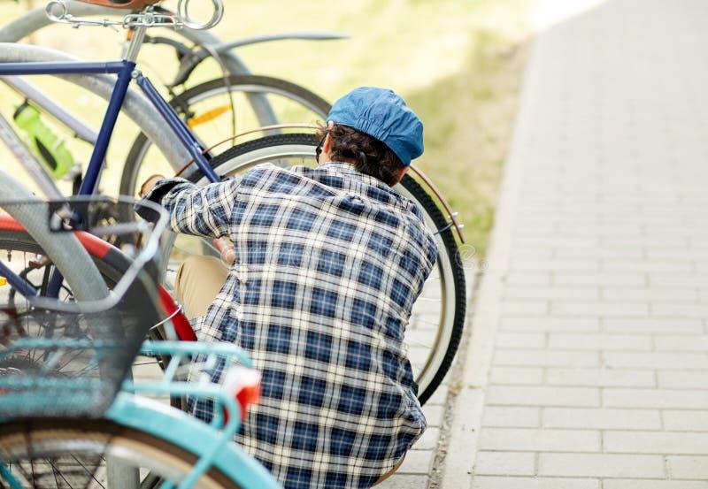 Serrure de bicyclette d'attache d'homme sur le stationnement de rue photographie stock