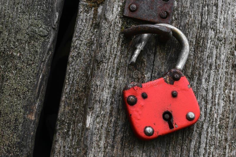 Serrure très vieille et rouge accrochant sur le mur en bois gris photos stock
