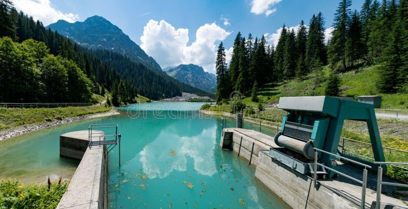 Serrures et déversoir d'un barrage sur un réservoir d'eau de lac de montagne coloré par turquoise photo libre de droits