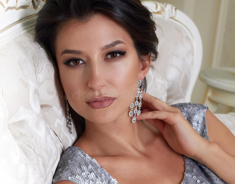 Sersualnaya beautiful young brunette woman with evening make-up chic groomed wearing a short evening dress embroidered with silver. Sequins and earrings sitting stock photo