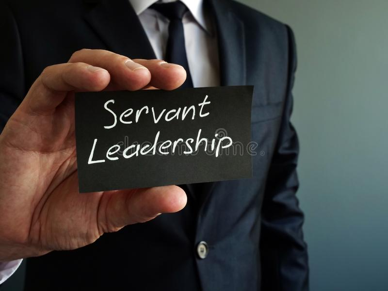 Servant leadership concept. Black piece of paper in the hand. S royalty free stock photos