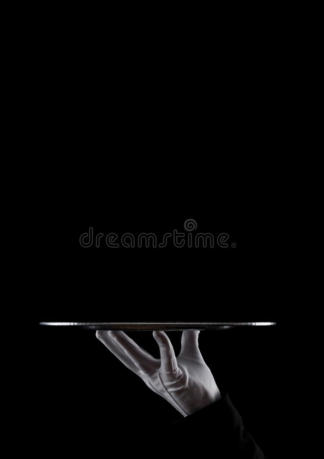 Servant white glove holds stainless steel tray. Servant wearing white glove holds stainless steel tray on black background stock photography