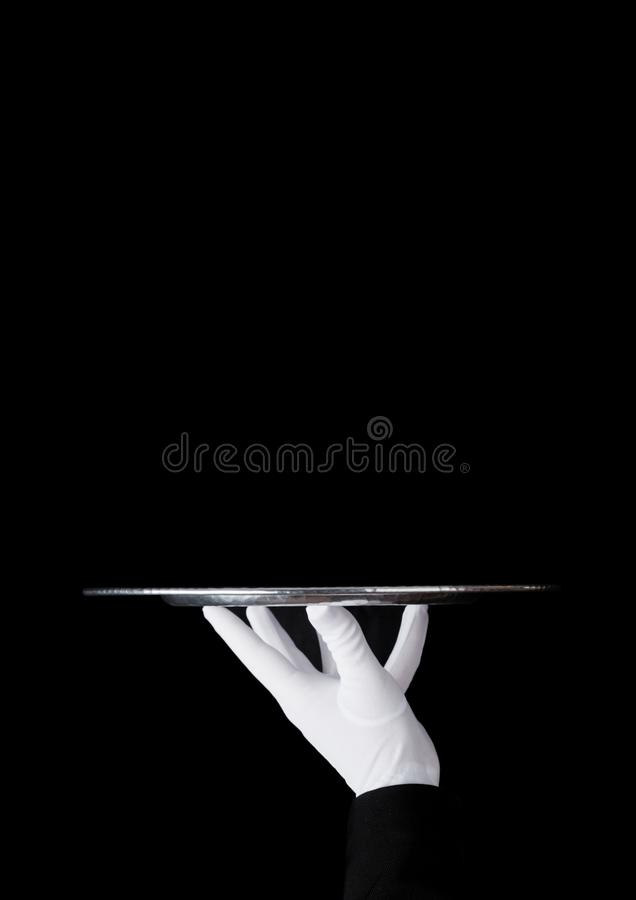 Servant white glove holds stainless steel tray. Servant wearing white glove holds stainless steel tray on black background royalty free stock image