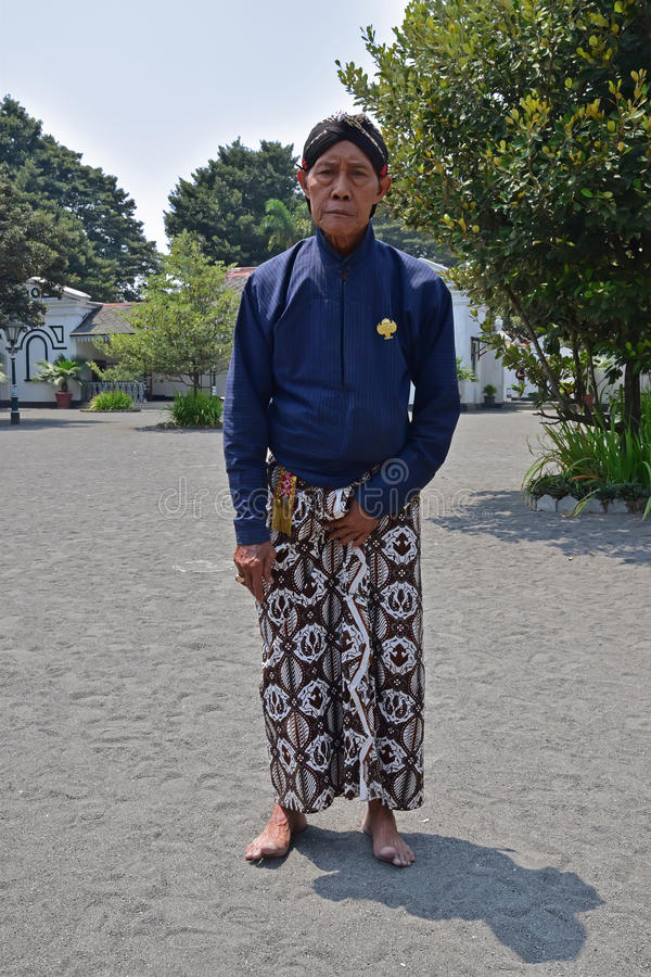 A servant of Yogyakarta Royal Palace Kraton posing in traditional attire royalty free stock photo