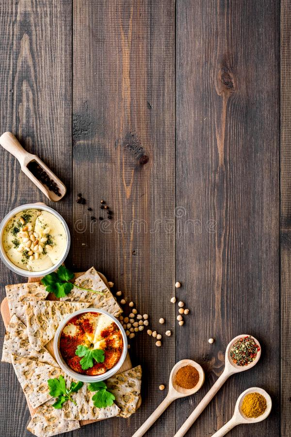 Serve hummus. Bowl with dish near pieces of crispbread on dark wooden background top view copy space stock photos