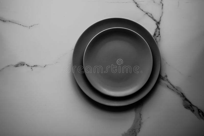 Serve the perfect plate. Black empty plate on marble, flatlay - stylish tableware, table decor and food menu concept. Serve the perfect dish stock photography