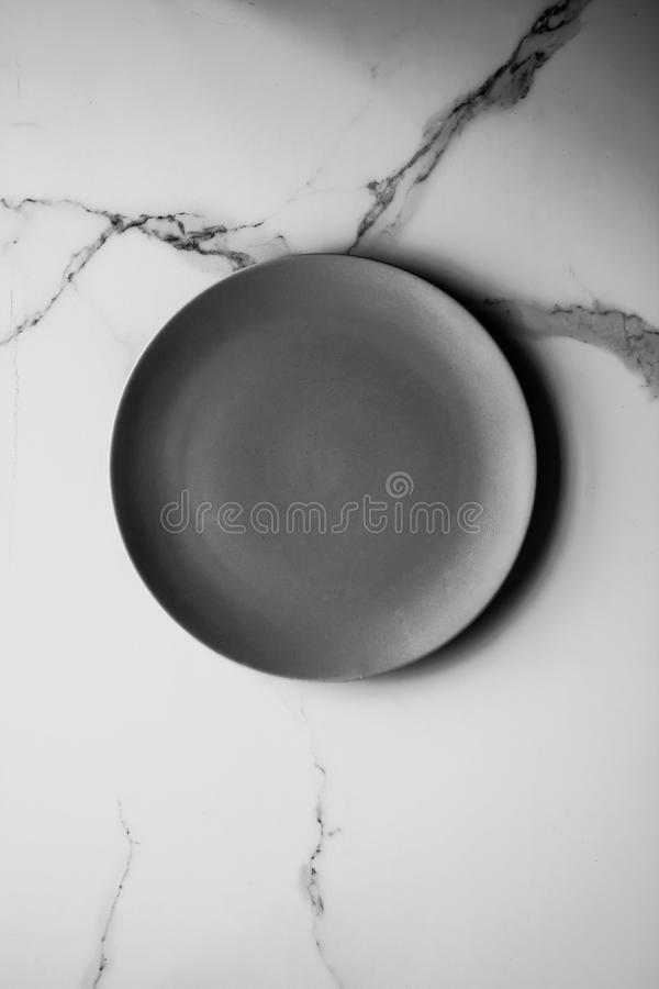 Serve the perfect plate. Black empty plate on marble, flatlay - stylish tableware, table decor and food menu concept. Serve the perfect dish royalty free stock photography