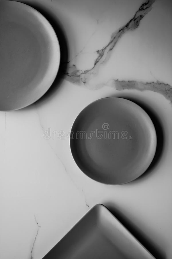 Serve the perfect plate. Black empty plate on marble, flatlay - stylish tableware, table decor and food menu concept. Serve the perfect dish royalty free stock photo