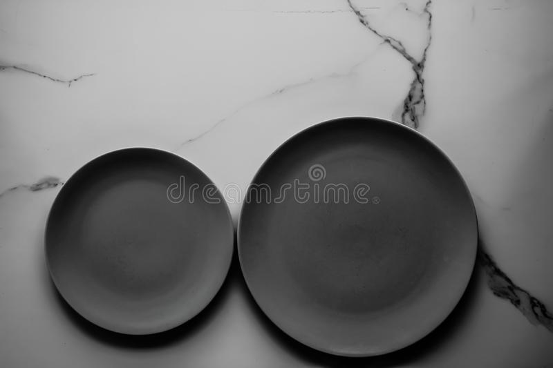 Serve the perfect plate. Black empty plate on marble, flatlay - stylish tableware, table decor and food menu concept. Serve the perfect dish royalty free stock photos
