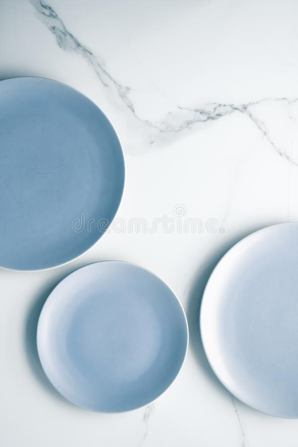 Serve the perfect plate. Blue empty plate on marble, flatlay - stylish tableware, table decor and food menu concept. Serve the perfect dish royalty free stock image