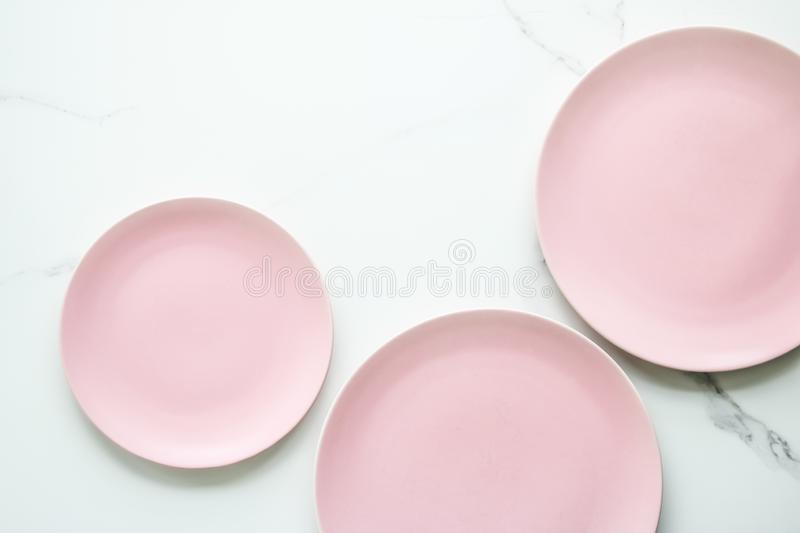 Serve the perfect plate. Pink empty plate on marble, flatlay - stylish tableware, table decor and food menu concept. Serve the perfect dish royalty free stock image