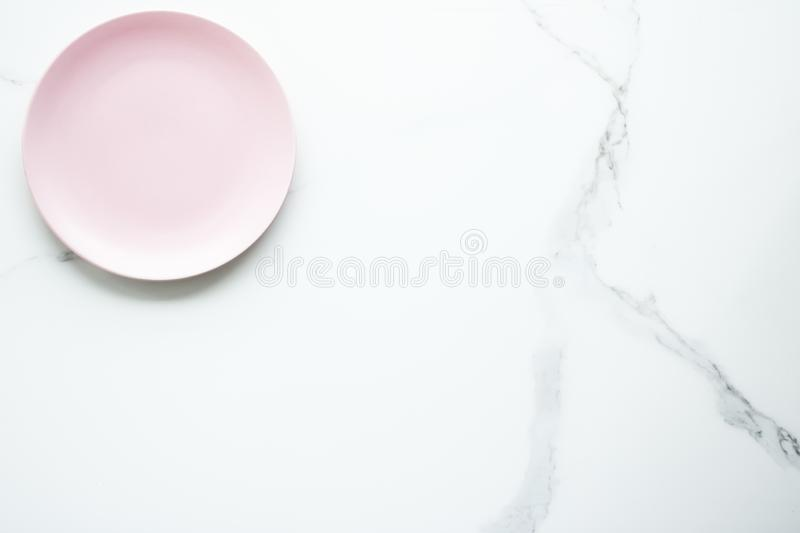 Serve the perfect plate. Pink empty plate on marble, flatlay - stylish tableware, table decor and food menu concept. Serve the perfect dish stock photo
