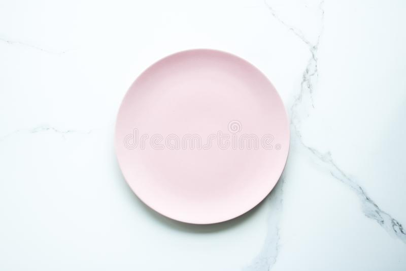 Serve the perfect plate. Pink empty plate on marble, flatlay - stylish tableware, table decor and food menu concept. Serve the perfect dish royalty free stock images
