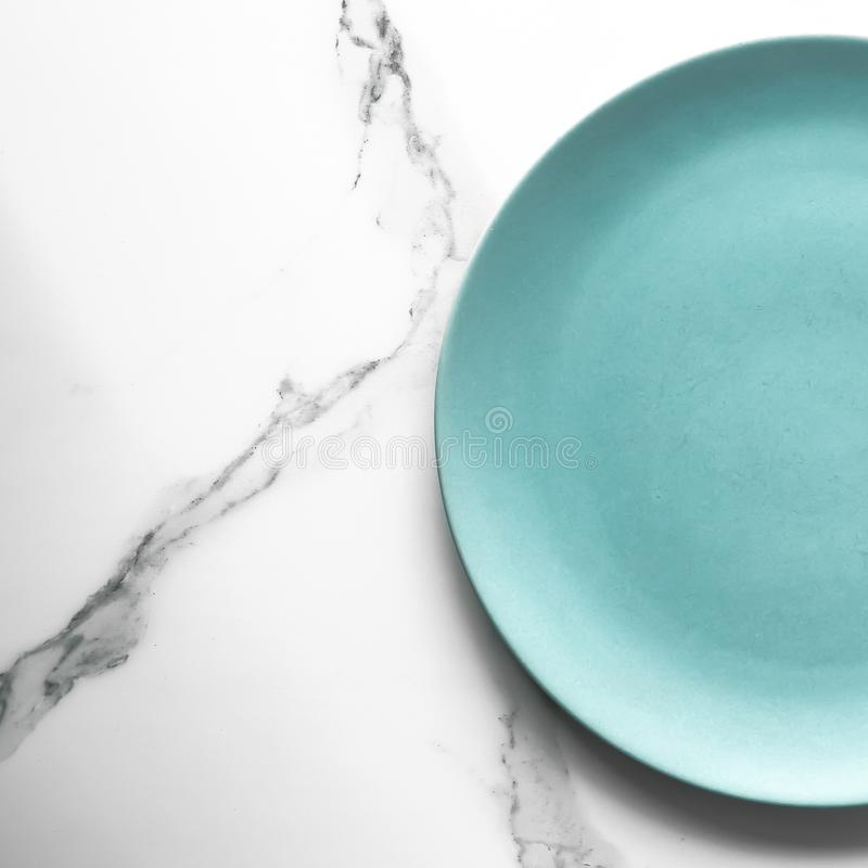 Serve the perfect plate. Turquoise empty plate on marble, flatlay - stylish tableware, table decor and food menu concept. Serve the perfect dish royalty free stock photos