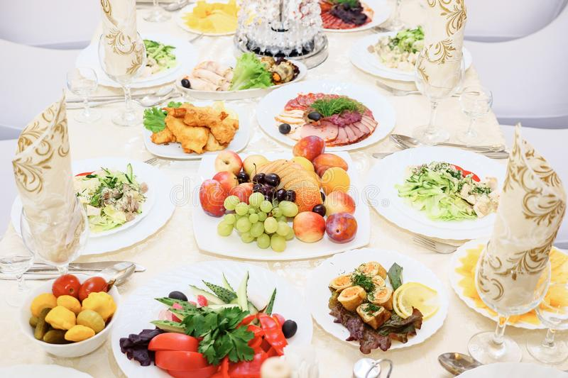 Served for a banquet table. Wine glasses with napkins, glasses, fruits and salads.  royalty free stock photos