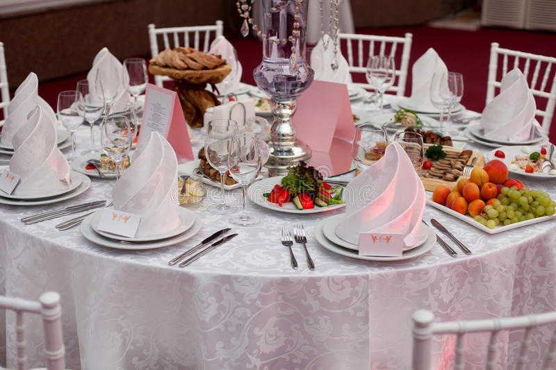 Served for a banquet table. Wine glasses with napkins, glasses. Served for a banquet table. Wine glasses with napkins, glasses and salads royalty free stock photos
