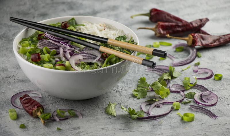 Served bowl of vietnamese soup pho ga with spring onion, chilli peppers and coriander on rustic background royalty free stock photos