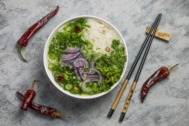 Served bowl of vietnamese soup pho ga with spring onion, chilli peppers and coriander on rustic background stock photography