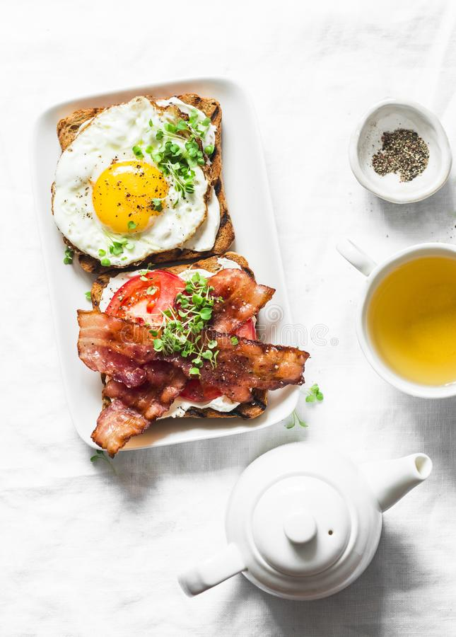 Served breakfast - toast with cream cheese, fried egg, tomatoes, bacon and green tea on a light background stock photo