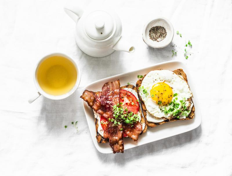 Served breakfast - toast with cream cheese, fried egg, tomatoes, bacon and green tea on a light background stock photography