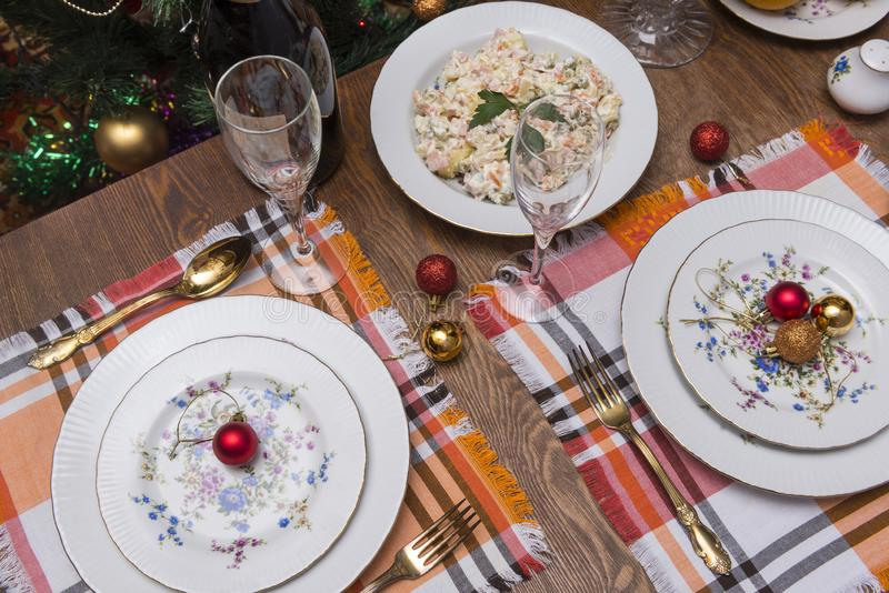 Served holiday table, plates, Cutlery, napkins, salad, Christmas. Balls, glasses, wine bottle, new year, Christmas royalty free stock photos
