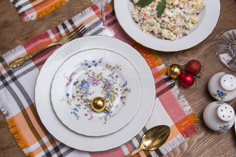 Served holiday table, plates, fork, Olivier salad, Christmas balls, napkins, salt shaker, new year, Christmas. Served holiday table, plates, fork, Olivier salad stock photography