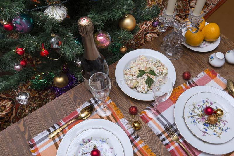 Served holiday table, plates, forks, glasses, Christmas balls, bottle of sparkling wine, Christmas tree, candles, tangerines, new. Year, Christmas royalty free stock photography