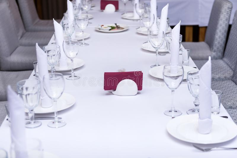Served table with white tablecloth, glass glasses, plates, red napkins. Served holiday table with white tablecloth, glass glasses, plates, red and white napkins stock photos