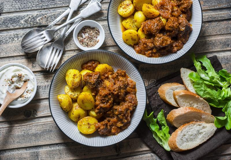 Served lunch table - irish beef stew with bombay turmeric potatoes. Delicious seasonal food on a wooden background, top view. Flat lay royalty free stock image