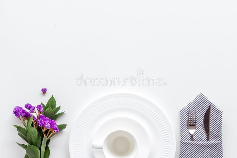 Elegant table setting with plates and tableware on white background top view copyspace. Served table. Elegant table setting with plates and tableware on white royalty free stock photo